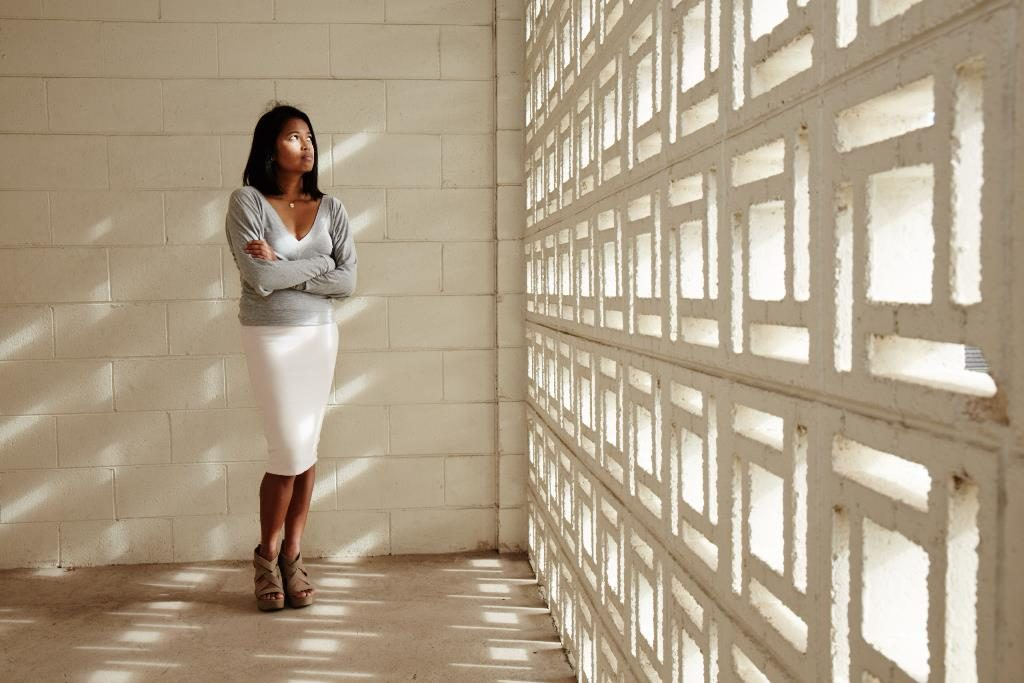 Artist Marakit Santiago standing in a white carpark looking out