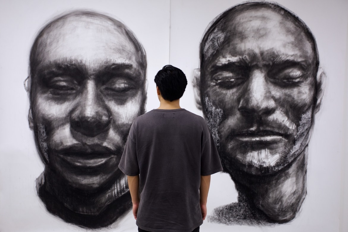 Artist standing and looking at his large-scale charcoal drawings on wall