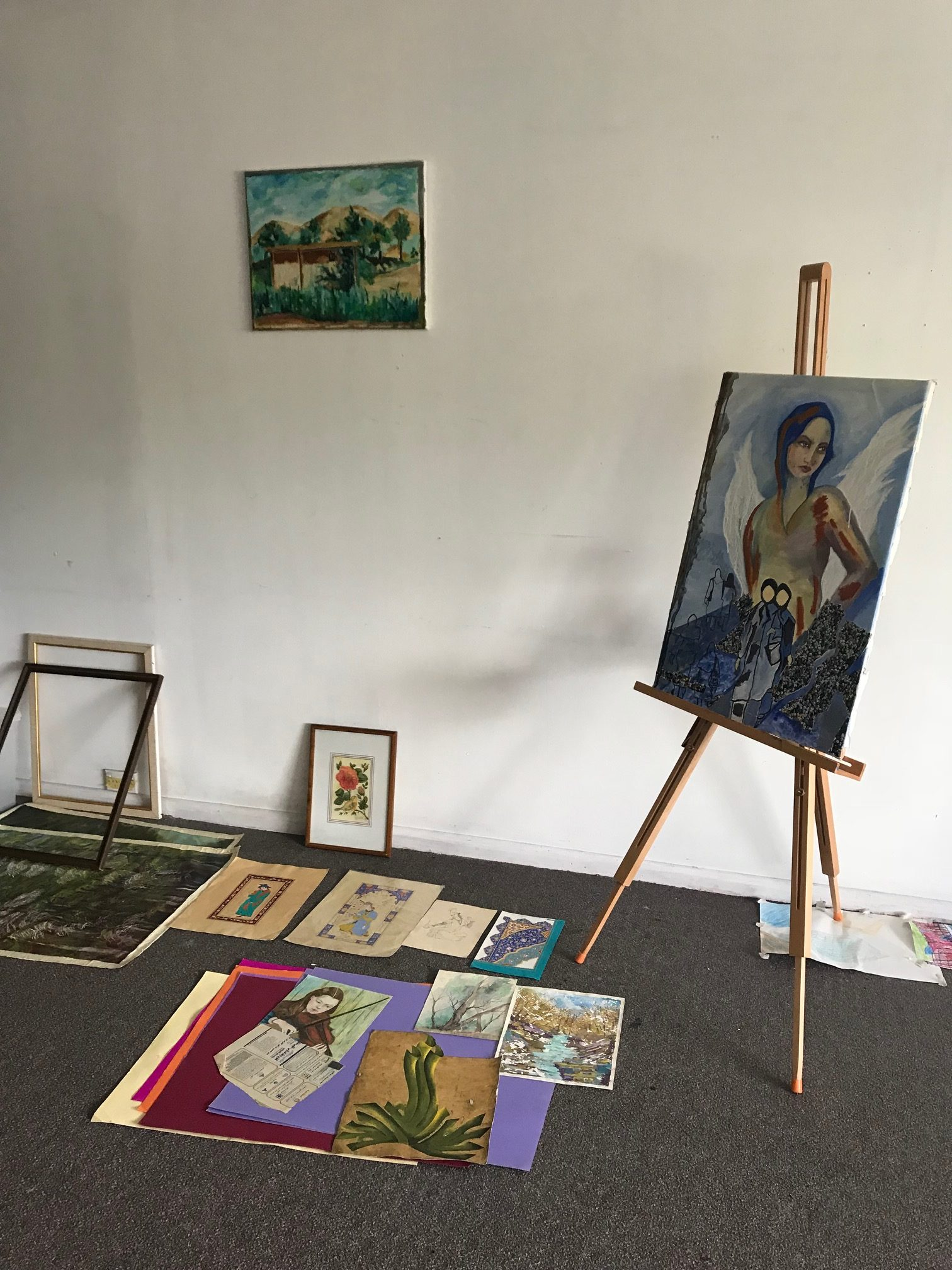 Miniature paintings on the ground, a painting on the wall and a painting on an easel of a woman