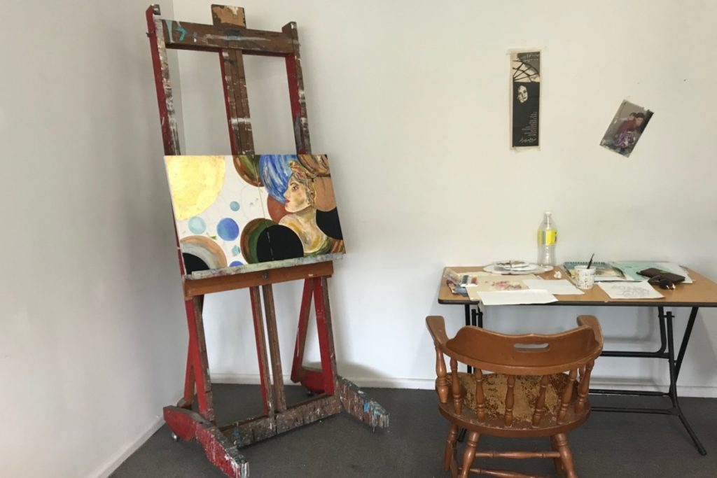 Painting on an easel next to a desk with painting materials and a chair