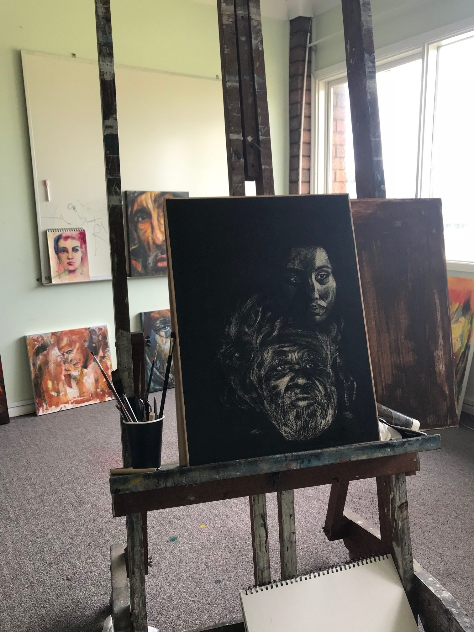 Painting on an easel in a studio of an Aboriginal man and a woman