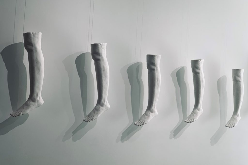 5 white porcelain casts of a human leg hanging along the side of a while wall. The shadow of the legs are cast on the flat wall behind.