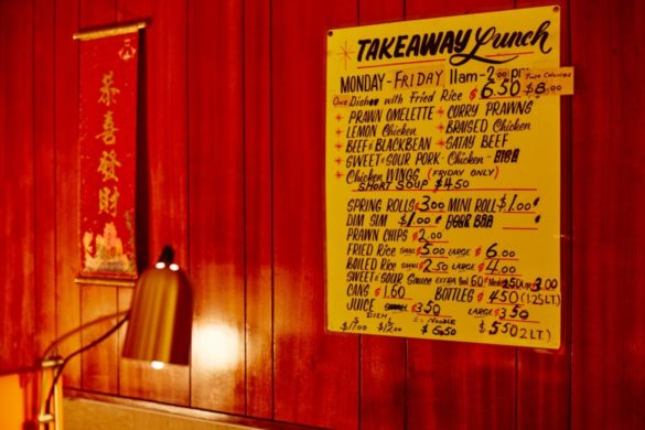 A lamp next to a red wall with a scroll and a takeaway lunch menu hanging.