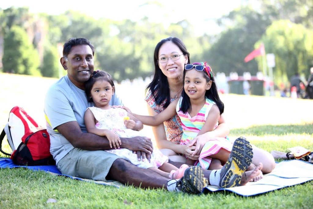 Family of two parents and two children sitting on grass
