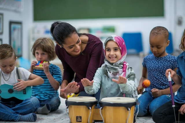 Young children playing musical instruments with teacher