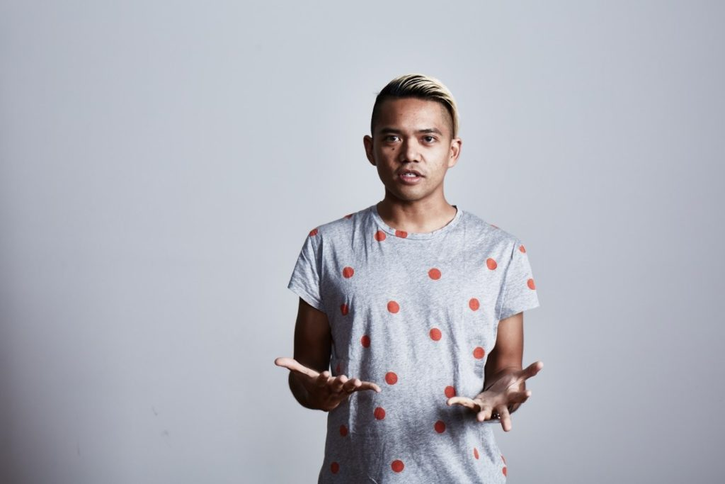 A man standing in front of a white wall in a grey tshirt with red polka dots telling a story.
