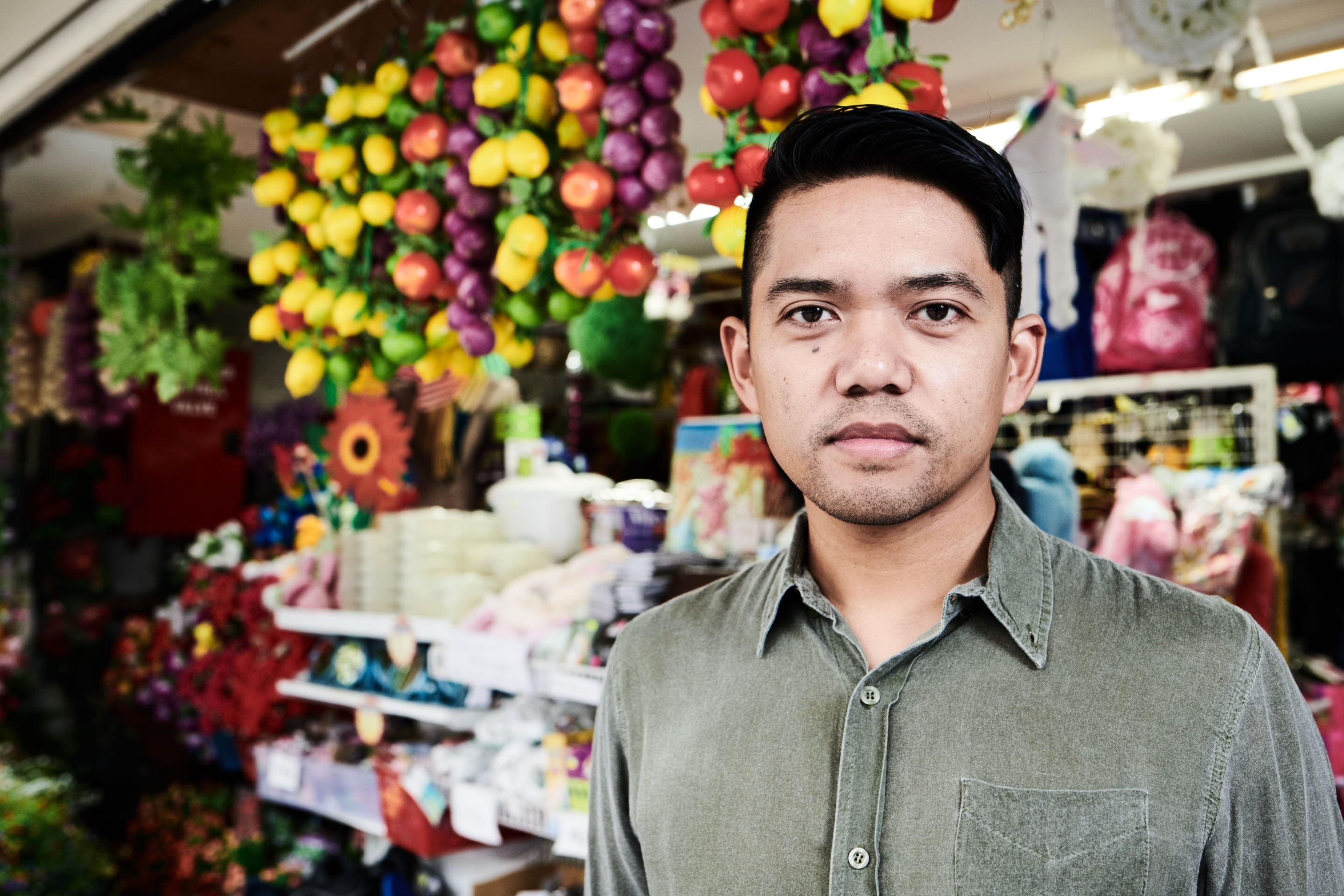 Man standing in front of a shop that has yellow, red and purple hanging plastic fruit