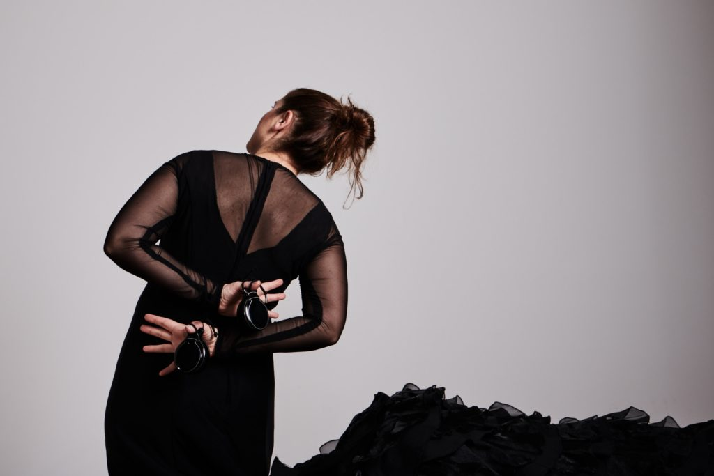 Woman in a black dress with her back to the camera flamenco dancing