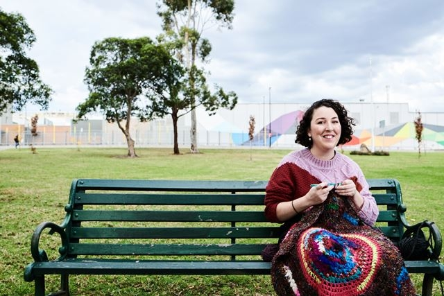 Women sits on a park bench with weaving materials