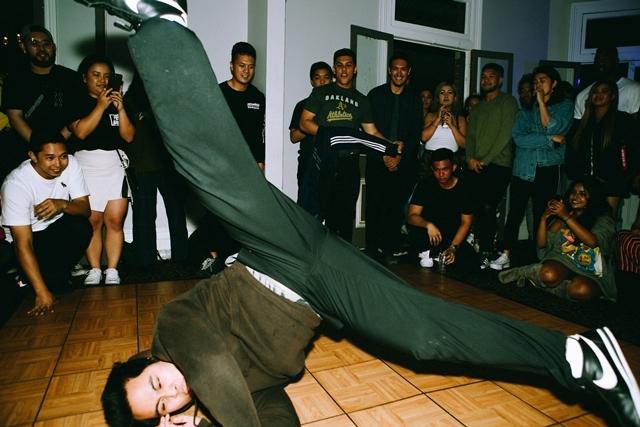 Man breakdancing while onlookers watch