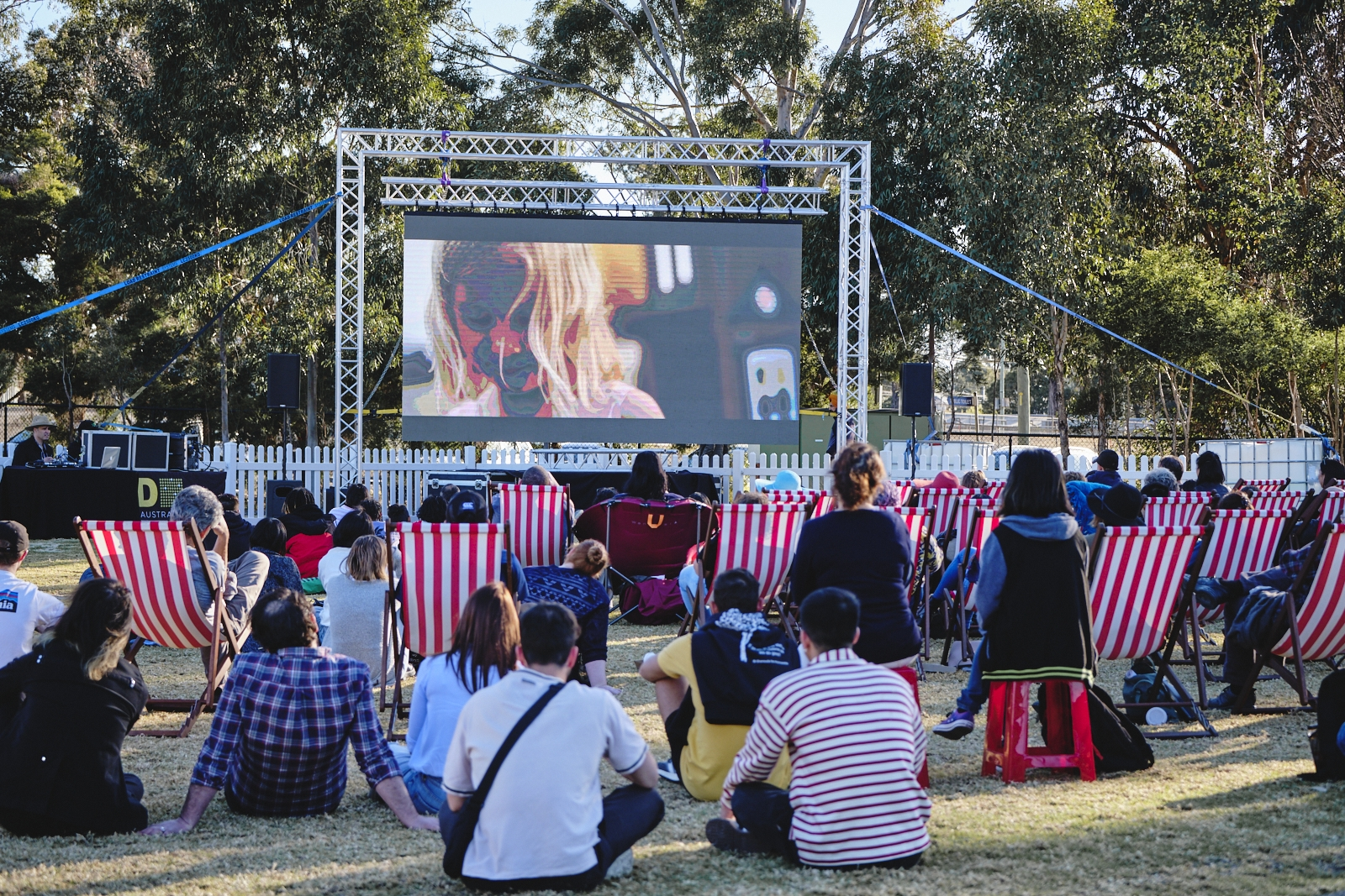 A large group of people sitting in front of a large screen with a film.