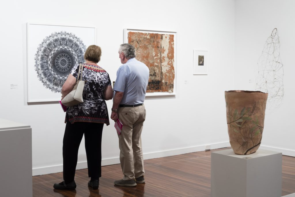 Two people viewing art displayed on a white wall