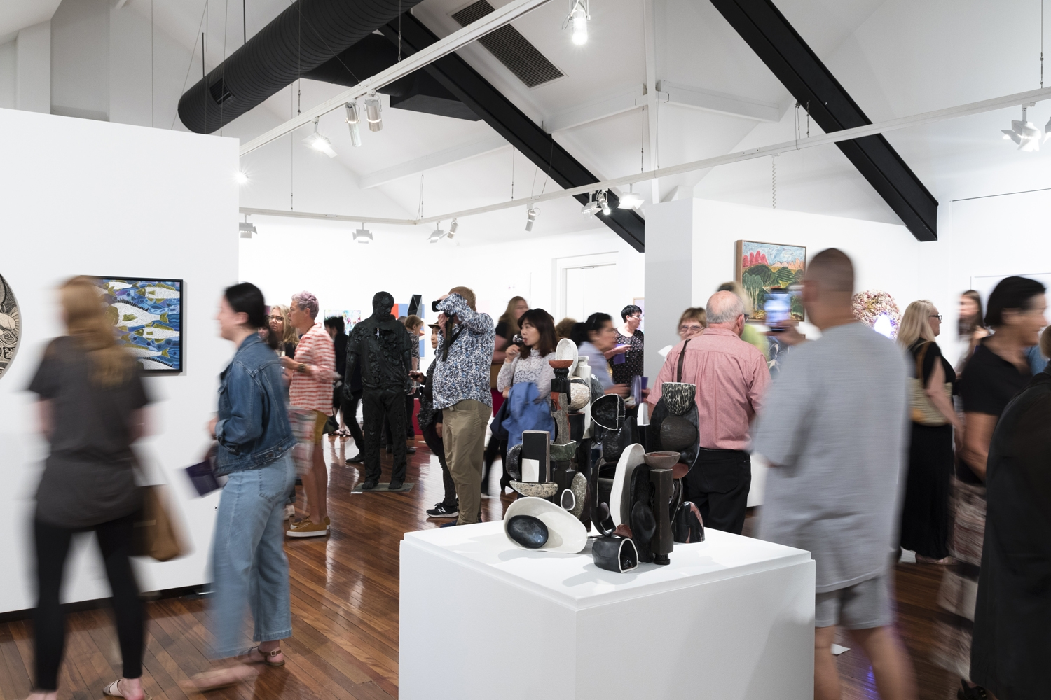 A crowd of people moving through a gallery space during an exhibition