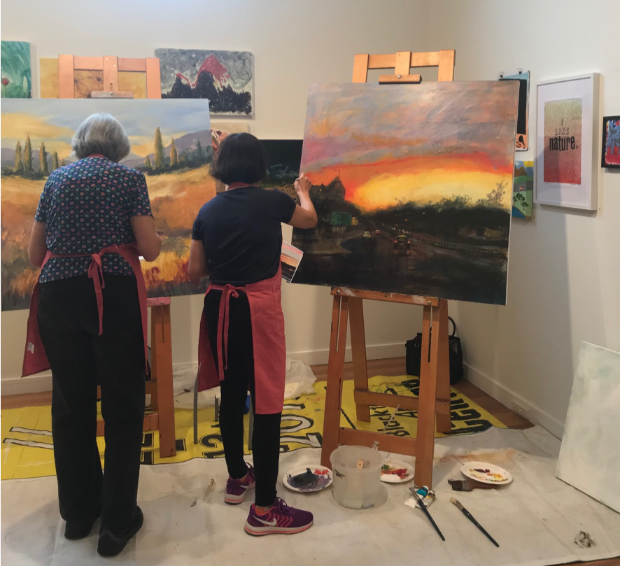 Two artists working on large scale canvases in the open studio