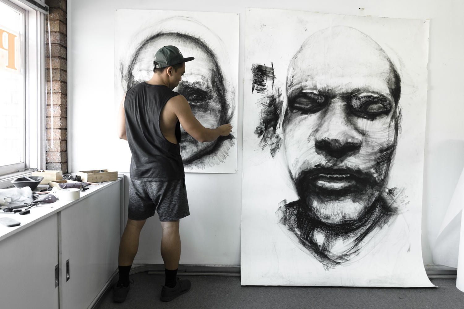 Kristone Capistrano working on his large scale charcoal drawings