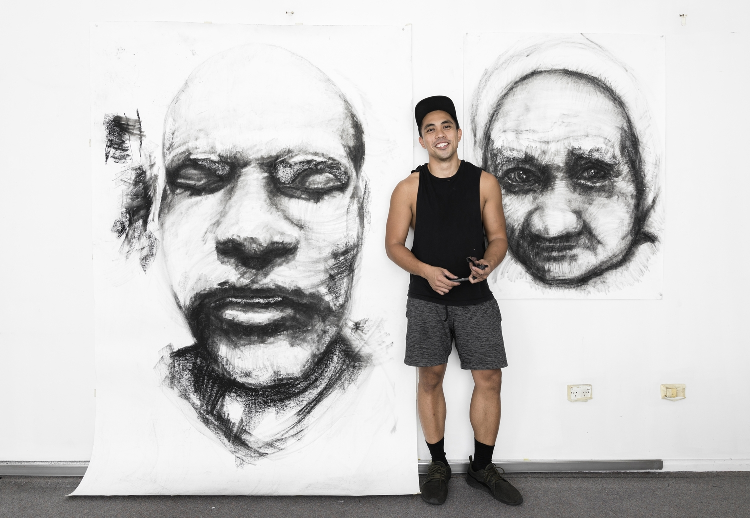 Artist Kristone Capistrano standing in front of two large scale charcoal drawings