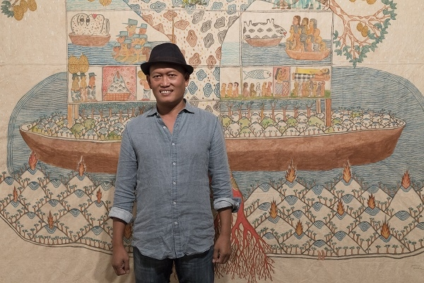 Jumaadi standing in front of his large scale painting