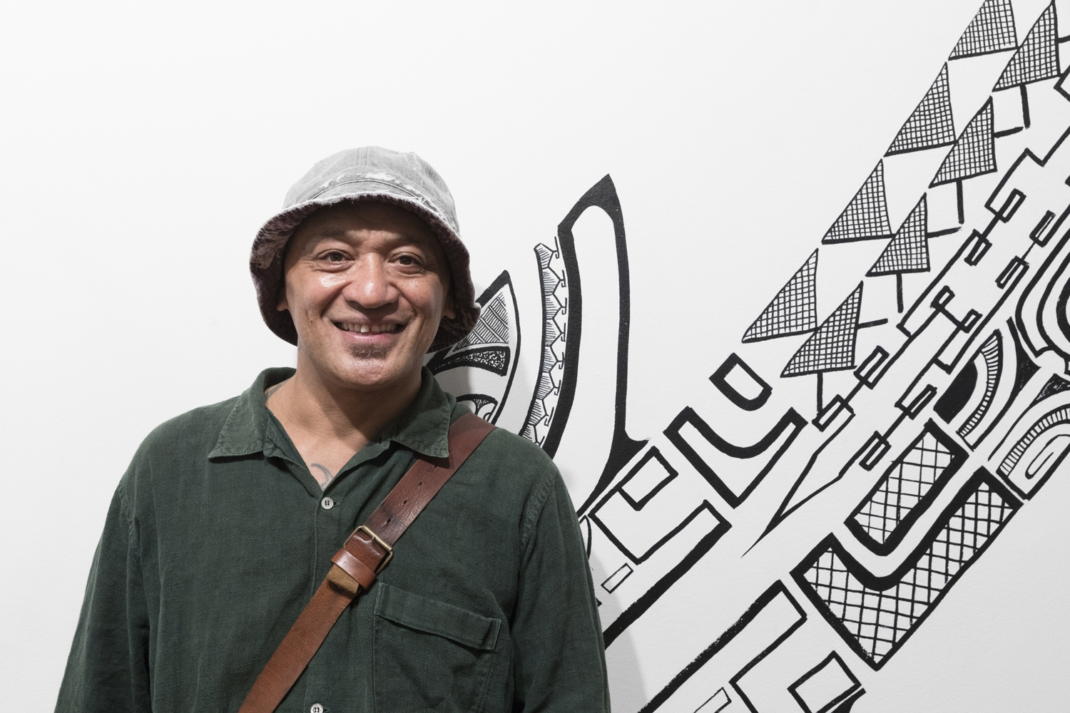 Teivao Tamariki standing in front of his artwork