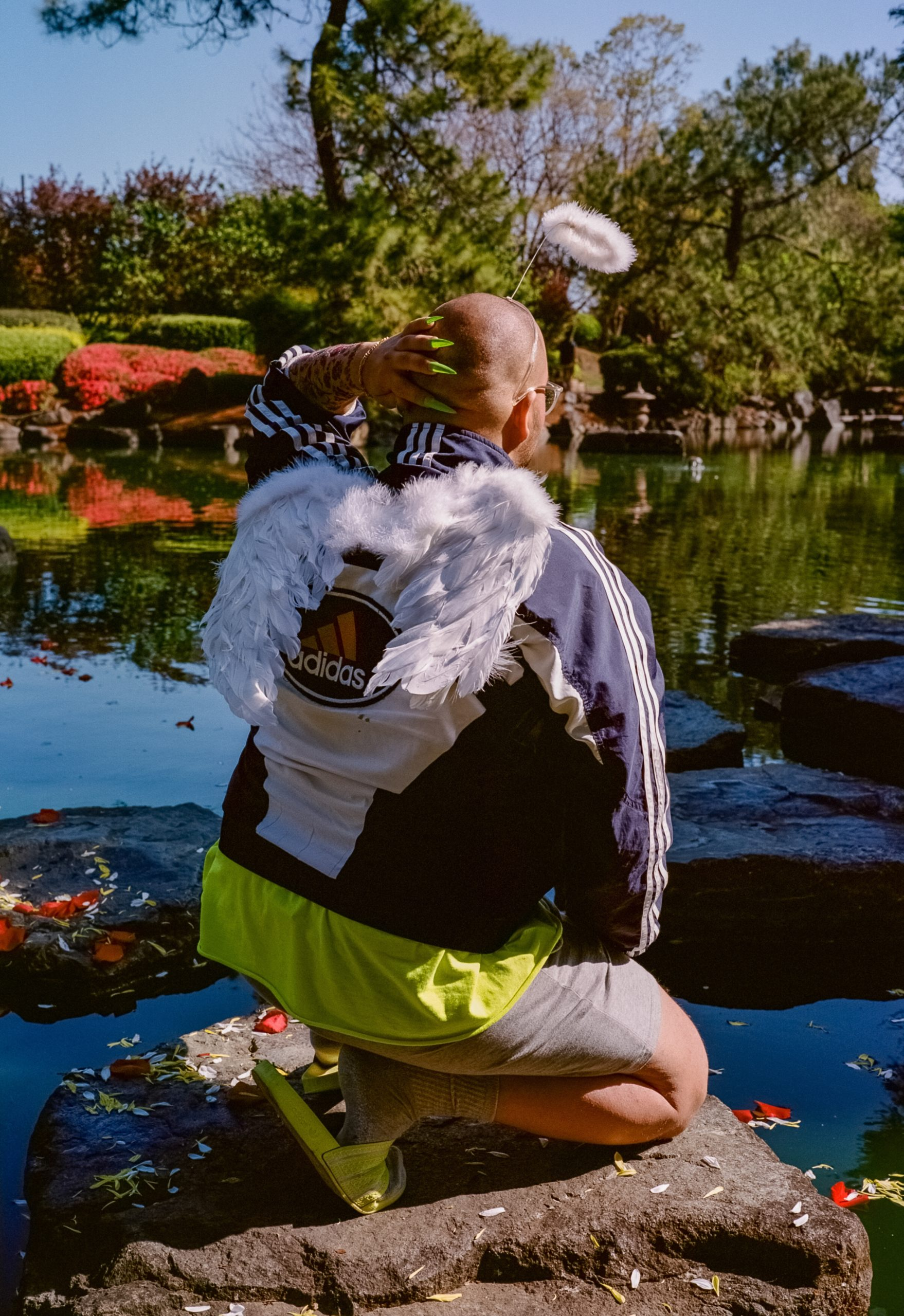 A figure is squatting on a stone with their back to the camera amidst the pond of the Auburn Botanic Japanese Gardens in this photographic portrait. Red, yellow and white flower petals line the pond and the stone. The colorful flora of the gardens can be seen in the background. The non-binary figure is wearing bright green acrylic nail clip-ons, a bright green t-shirt, bright green slides, and a navy blue Adidas wind-breaker. Feathered wings adorn their back, a toy-store halo is floating above their head, and fake tattoos are lined down their fore-arm. Their hand is raised and resting behind their head.