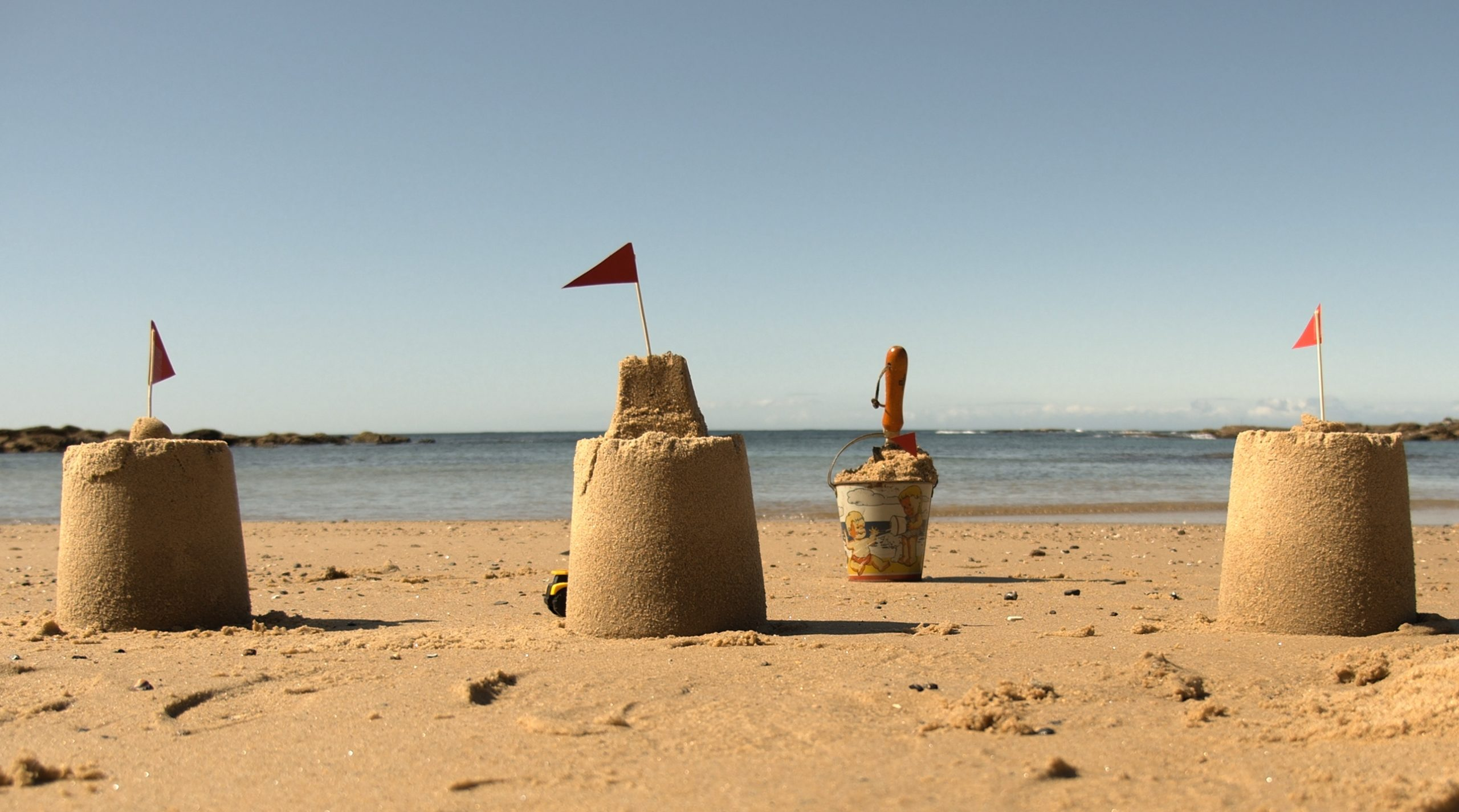 Four sandcastles on the beach to promote free drama workshop