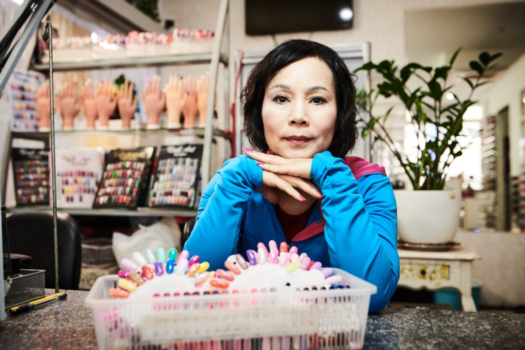 Artist Mary Nguyen sitting in a nail salon with her hands under her chin