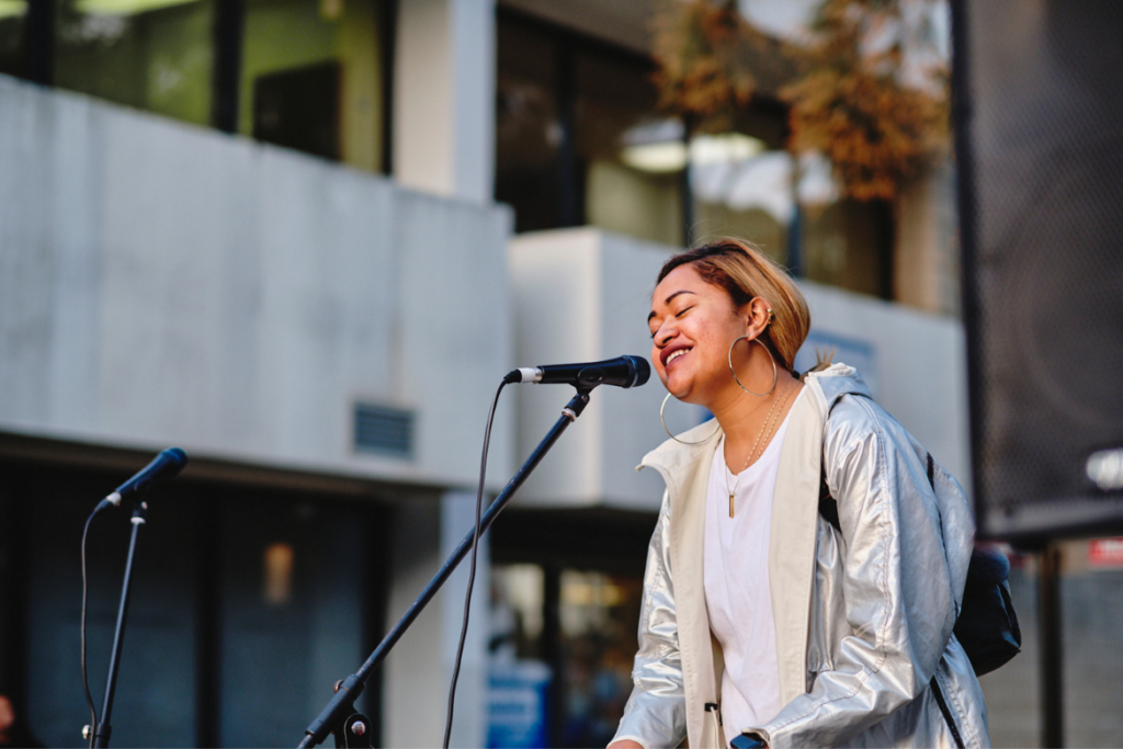 A Pacific Islander woman in a white shirt and grey jacket performing with a microphone