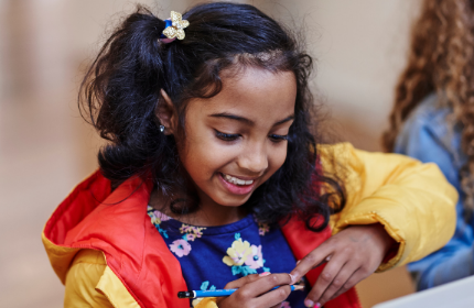 Young girl holding pencil and smiling
